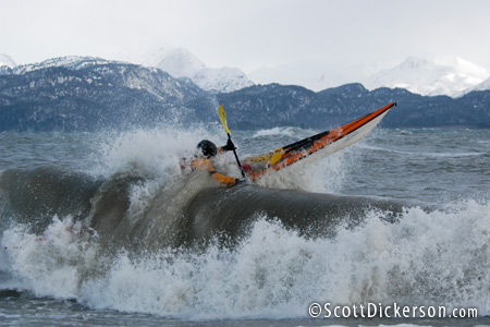 Sea kayak surfing in winter, Kachemak Bay, Alaska.