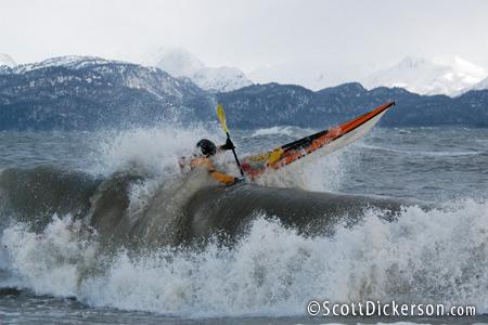 Sea kayak surfing in winter, Kachemak Bay, Alaska.