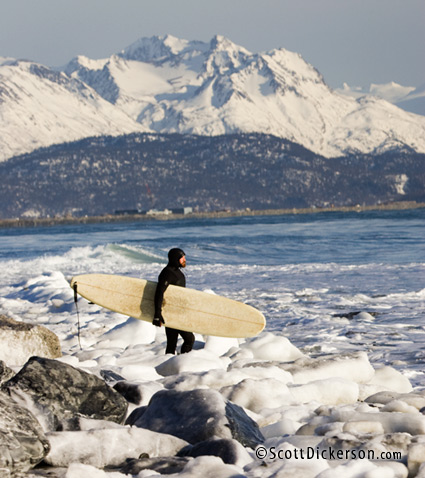 Alaskan surfer Ty Gates walks through chunks of ice on the beach.