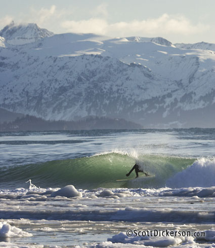 Photo of Alaskan surfer Gart Curtis surfing during the icy winter in Homer, Alaska.