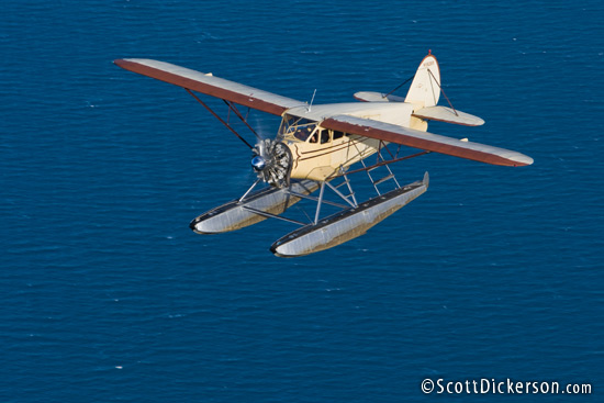 Air to air aerial photo of 1933 Stinson JR SR on floats flying over Kachemak Bay, Alaska.