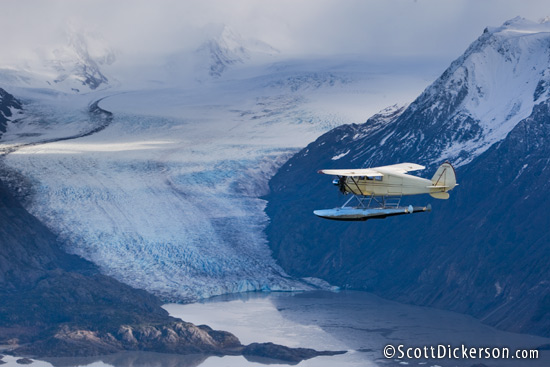 Air to air aerial photo of 1933 Stinson JR. SR floatplane flying by Grewingk Glacier and the Kenai Mountains, Alaska.
