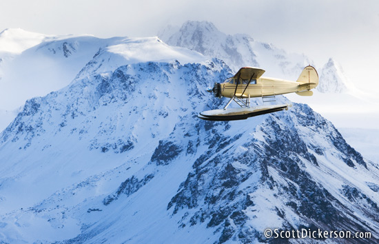 Air to air aerial photo of 1933 Stinson Jr. Sr floatplane flying through Kenai Mountains, Alaska.