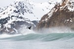 Ian Walsh surfing in Alaska beneath snow covered mountains.