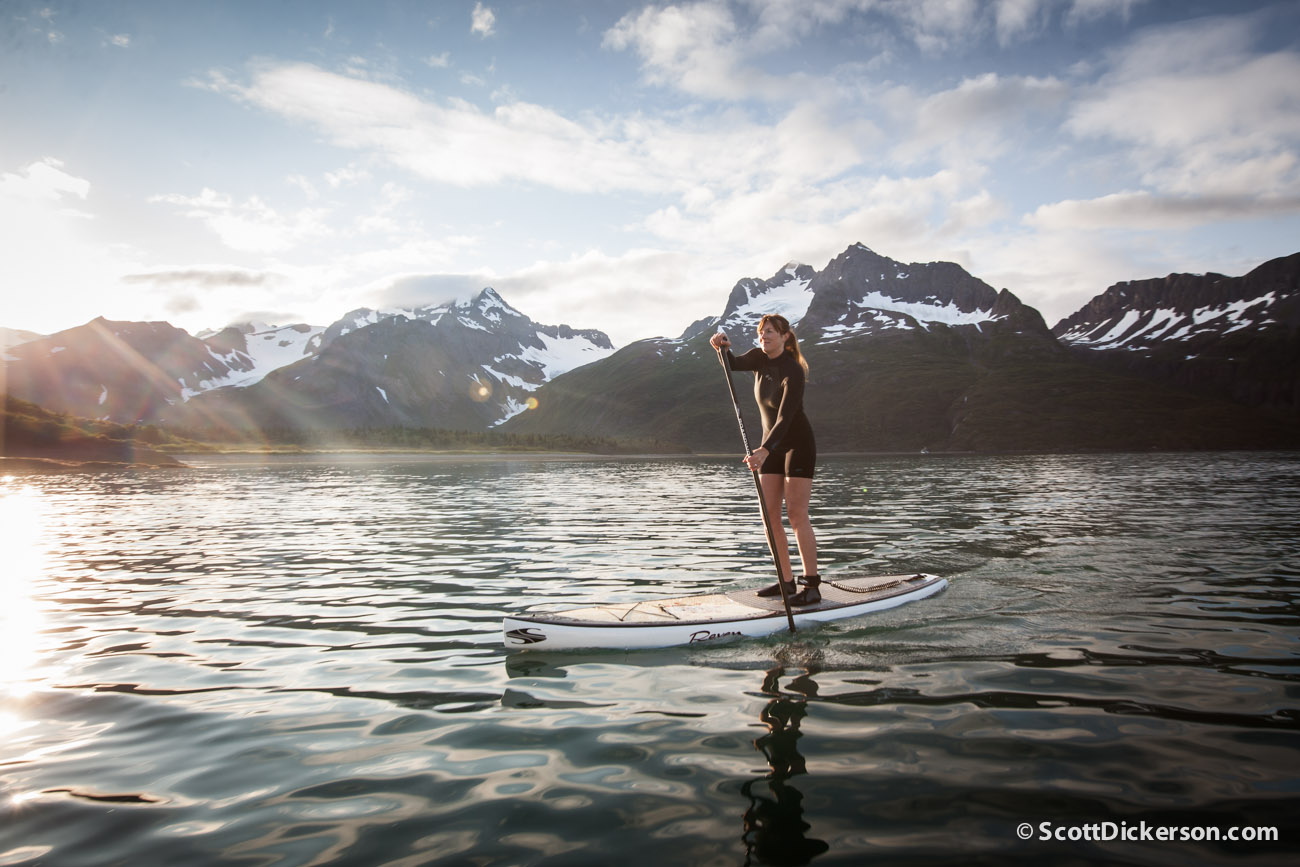 stand up paddleboarding in Alaska on a glassy day with mountains and glaciers.