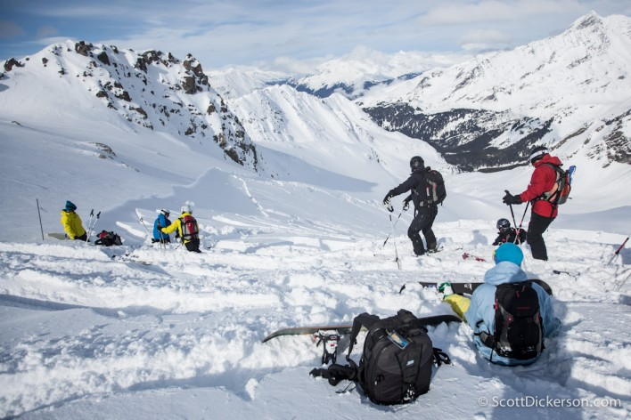 Skiiers watch as an avalanche slides below them while heliskiing in Alaska.