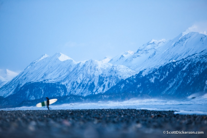 surfing in Alaska with snow covered mountains