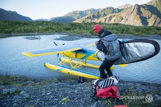 Jason McCaffrey loading his kitesurfing gear into a seaplane after kitesurfing in a glacial lake in Alaska.