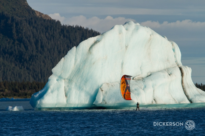Jason Slezak, kitesurf ambassador for Patagonia, kiting near a huge iceberg in a glacial lake in Alaska.